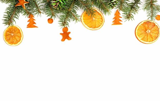 Weihnachtsgrenze - grüne tannenzweige, verziert mit getrockneten orangen, gemalten kegeln und getrockneter orange