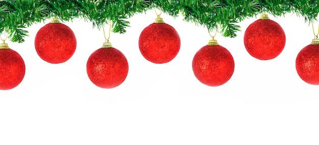 Weihnachtsgrenze ihrer nadelbaumzweige mit hängenden roten kugeln lokalisiert auf weißem hintergrund
