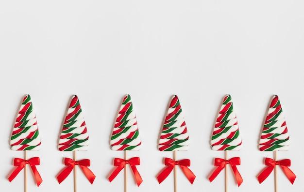 Weihnachtsgrenze mit süßigkeiten in form eines weihnachtsbaums auf weißem hintergrund.