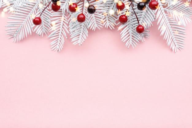 Weihnachtsgrenze mit tannenzweigen, eberesche und goldenen lichtern auf pastellrosa hintergrund, kopienraum