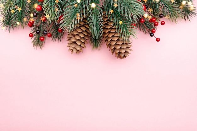 Weihnachtsgrenze mit tannenzweigen, nadelbaumkegeln, roten beeren und goldenen lichtern