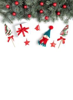 Weihnachtsgrenze mit tannenzweigen schneemannlutschern und weihnachtsschmuck auf einem weiß