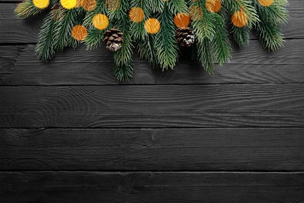 Weihnachtsgrenze mit tannenzweigen und zapfen auf schwarzem hölzernem hintergrund