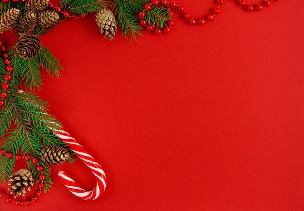 Weihnachtsgrenzkomposition mit zuckerstange auf rotem hintergrund.