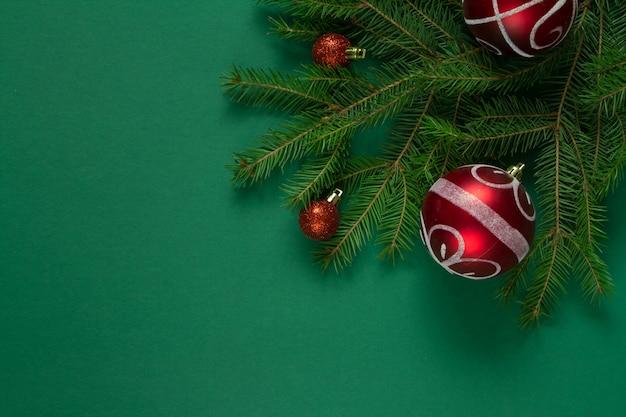 Weihnachtsgrüne fichtenzweige und rote weihnachtsblasen