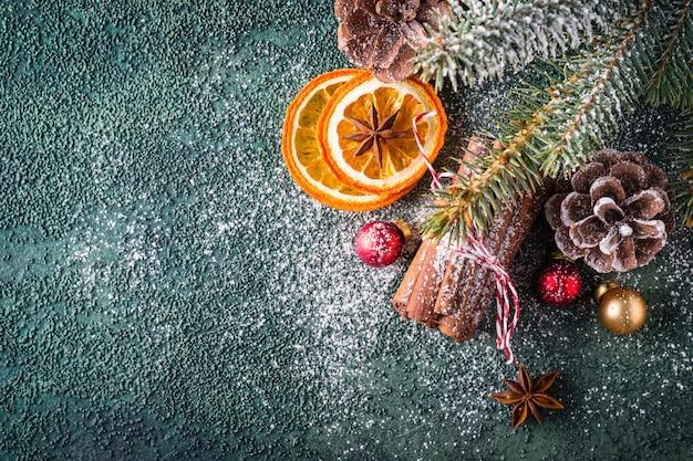 Weihnachtsgrüner hintergrund. komposition mit trockenen orangen und zimtstangen