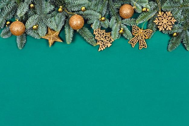 Weihnachtsgrüner hintergrund mit goldenen spielzeugen.