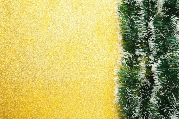Weihnachtsgrünes lametta auf gold glitzert