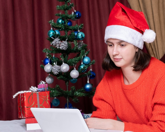 Weihnachtsgrüße im internet, bildung, online-shopping. mädchen in einer weihnachtsmannmütze mit einem laptop zu hause, geschmückter weihnachtsbaum, geschenke. frohe weihnachten und neujahr konzept