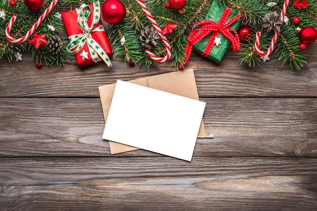 Weihnachtsgrußkarte auf hölzernem hintergrund. attrappe, lehrmodell, simulation. flach liegen. draufsicht mit kopierraum