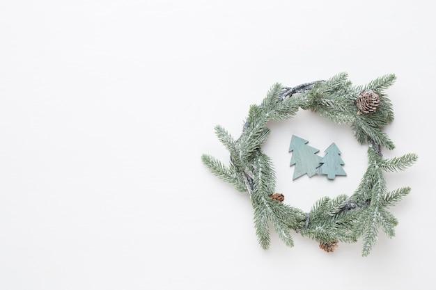 Weihnachtsgrußkarte. kranzdekoration auf weißem hölzernem hintergrund.