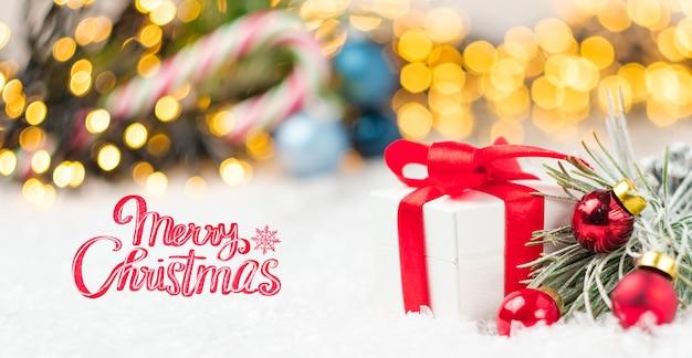 Weihnachtsgrußkarte mit geschenkboxen und rotem band auf dem schnee