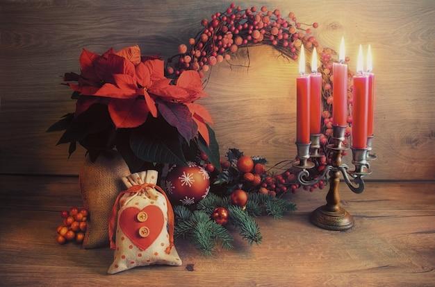 Weihnachtsgrußkarte mit kerzen und verziertem weihnachtsbaum auf holz