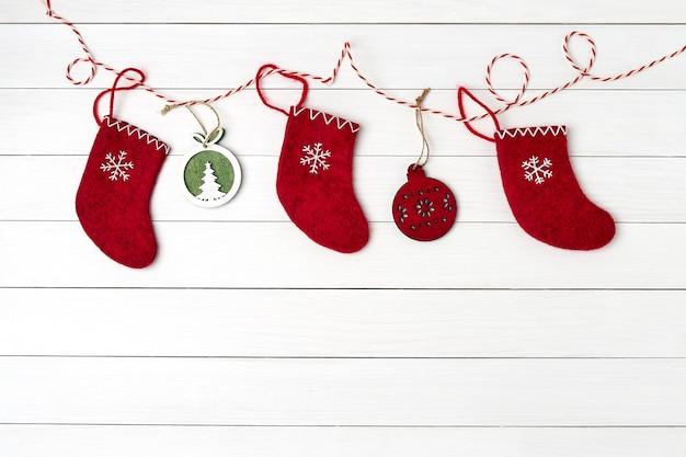 Weihnachtsgrußkarte. weihnachtsrote socken auf weißem hölzernem hintergrund. textfreiraum, ansicht von oben