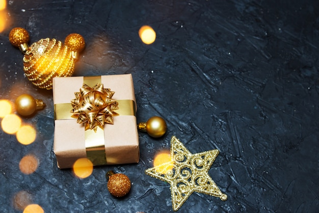 Weihnachtsgrußkarte zusammensetzung. geschenk mit goldener weihnachtsdekoration mit licht auf dunkelblauem hintergrund