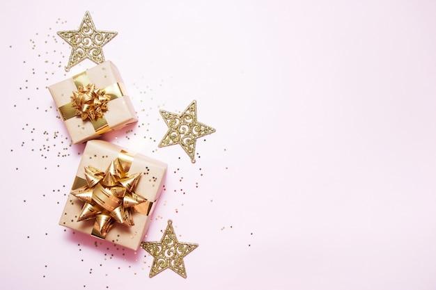 Weihnachtsgrußkarte zusammensetzung. kraftpapiergeschenk mit goldener ball-, konfettistern- und golddekoration auf rosa hintergrund