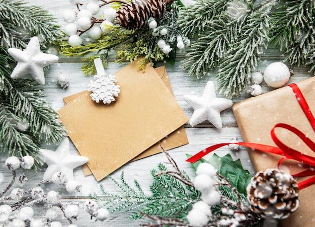 Weihnachtsgrußkartenbrief im umschlag mit baum, flatlay auf einem weißen hölzernen hintergrund, mit platz für ihren text, flat lay, draufsicht