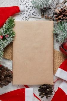 Weihnachtsgrußkartenbuchstabe auf bastelpapierumschlag mit pelzbaumzweig-flatlay auf einem hölzernen hintergrund