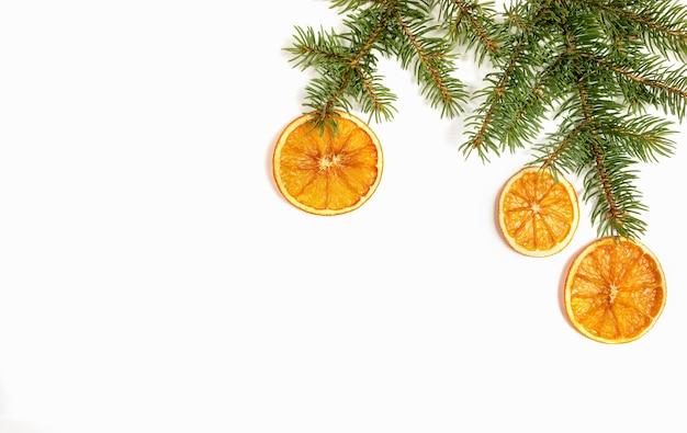 Weihnachtshandgemachte dekorationen. grüne tannenzweige mit den getrockneten orange scheiben lokalisiert auf weiß mit kopienraum.