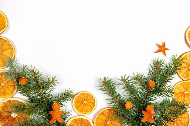 Weihnachtshandgemachte dekorationen von tannenzweigen, getrocknete orangen, getrocknete figuren der orange schale auf weiß. draufsicht, kopie, raum.