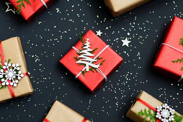 Weihnachtshandgemachte rote geschenkboxen auf draufsicht des dunklen hintergrundes