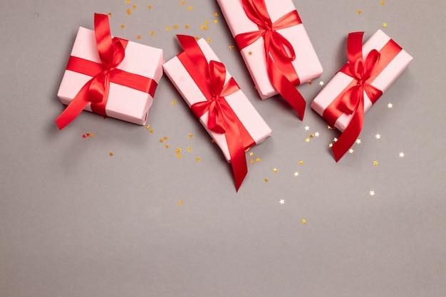 Weihnachtshandwerks-überraschungsgeschenkboxen mit roten bändern und goldenen sternen funkeln auf grauer, draufsicht. neujahr.