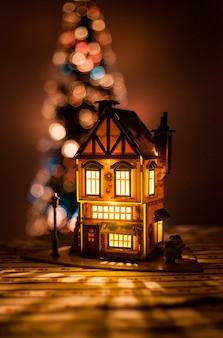 Weihnachtshaus mit eigenen händen aus pappe und papier, ein haus mit einer glühbirne und einem weihnachtsbaum