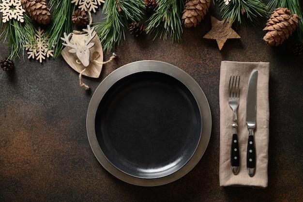 Weihnachtshaus tischdekoration mit teller und holzdekoration auf braun.