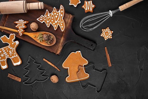 Weihnachtshausgemachte lebkuchengewürze und schneidebrett auf dunklem hintergrund mit kopienraum f...
