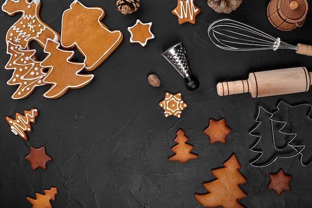 Weihnachtshausgemachte lebkuchenplätzchen, gewürze und schneidebrett auf dunklem hintergrund mit kopienraum für textdraufsicht. urlaub, feiern und kochkonzept. neujahrs- und weihnachtspostkarte