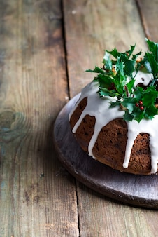 Weihnachtshausgemachter dunkler schokolade bundt kuchen, der mit weißer zuckerglasur und stechpalme verziert wird, beeren niederlassungen auf einem rustikalen alten hölzernen