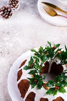 Weihnachtshausgemachter dunkler schokolade bundt kuchen verziert mit stechpalmenbeerenzweigen auf stein