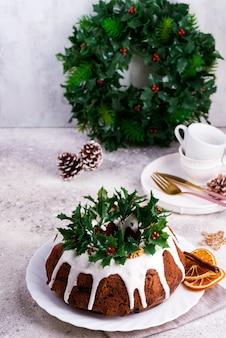 Weihnachtshausgemachter dunkler schokolade bundt kuchen verziert mit weißer zuckerglasur und stechpalmenbeerenniederlassungen auf einem leichtbeton