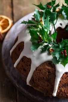 Weihnachtshausgemachter dunkler schokolade bundt kuchen verziert mit weißer zuckerglasur- und stechpalmenbeerenniederlassungsnahaufnahme