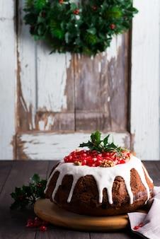 Weihnachtshausgemachter schokoladenkuchen verziert mit weißen zuckerglasur- und granatapfelkernen gegen von den alten holztüren