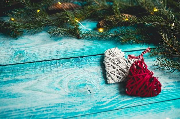 Weihnachtsherzen auf einem blauen holztisch mit weihnachtsbaum. attrappe, lehrmodell, simulation.