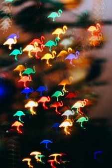 Weihnachtshintergrund, bokeh in form eines rosa flamingos. hintergrundunschärfe