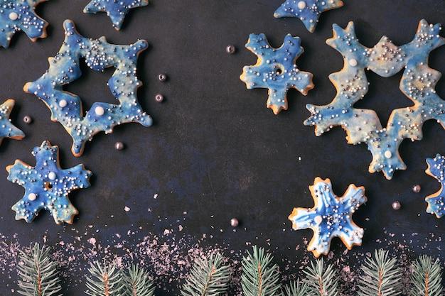 Weihnachtshintergrund, ebenenlage mit schneeflocken- und sternplätzchen auf dunkelheit