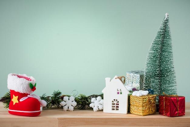 Weihnachtshintergrund. ein kleiner weihnachtsbaum und kisten mit geschenken auf einem holztisch. grüner hintergrund. platz für text.