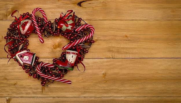 Weihnachtshintergrund ein mit gestreiften lutschern verziertes herz, eine girlande und weihnachtliches rotes spielzeug