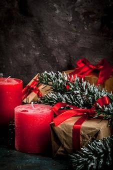 Weihnachtshintergrund für grußkarte. weihnachtsbaumaste mit schneeeffekt mit festlichem rotem band, kiefernkegeln, geschenkboxen und kerzen, auf dunkelblauem hintergrund