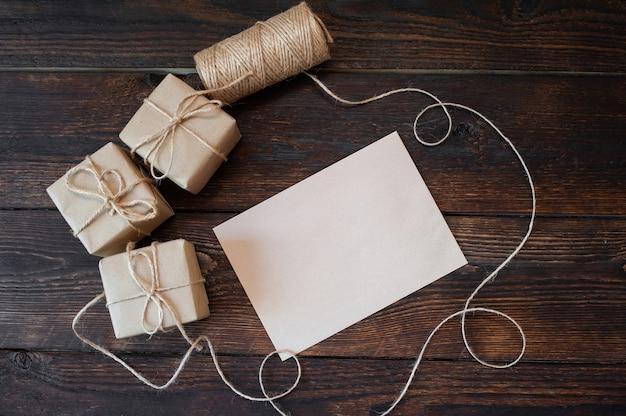 Weihnachtshintergrund für grußkartenblatt papier mit platz für text. weihnachtsgeschenkboxen auf hölzernem hintergrund.