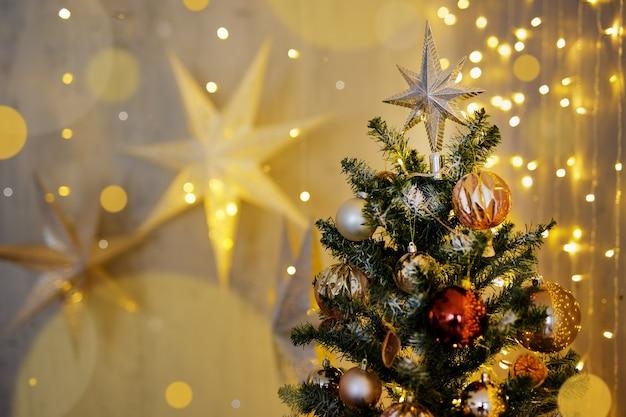 Weihnachtshintergrund - geschmückter weihnachtsbaum mit festlichen girlandenlichtern und papiersternen