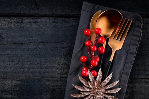 Weihnachtshintergrund - goldenes besteck auf leinenserviette und schwarzem hölzernem hintergrund, freier raum für ihren text.