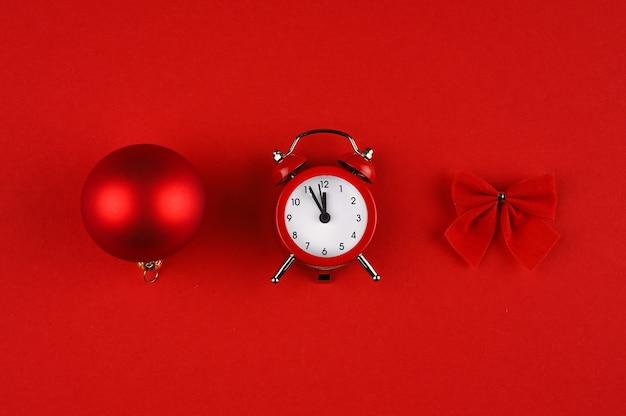 Weihnachtshintergrund in den roten schattierungen mit wecker, weihnachtsball und bogen.
