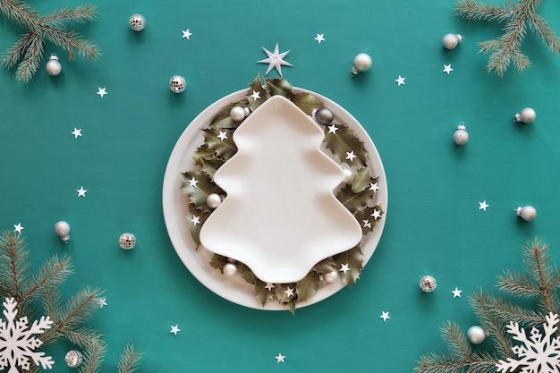 Weihnachtshintergrund in grün und weiß. weihnachtsbaumformplatte mit kopierraum auf tisch bedeckt mit grünem minztextil. tannenzweige und weiße verzierungen. holly geht auf einen runden teller.
