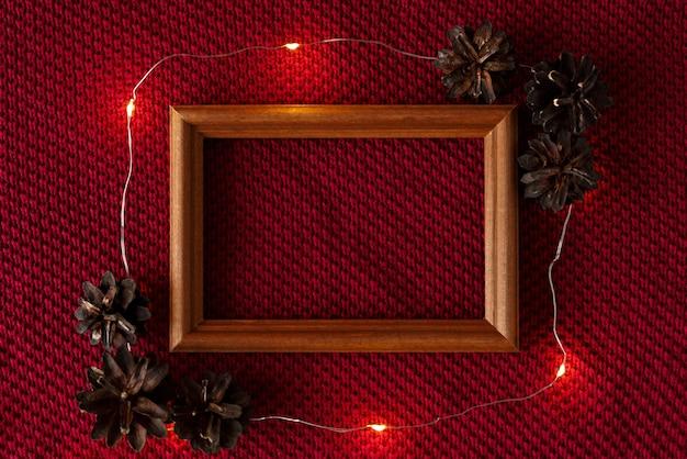 Weihnachtshintergrund kegelrahmen und girlande liegen auf der gestrickten textur eines pullovers