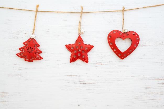 Weihnachtshintergrund - metallrustikale weihnachtsverzierung, die am weißen holz hängt