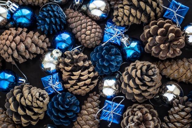 Weihnachtshintergrund mit blauen verzierungen und schneebedecktem tannenzapfen. weihnachtsfeierdekoration mit glänzenden kugeln.