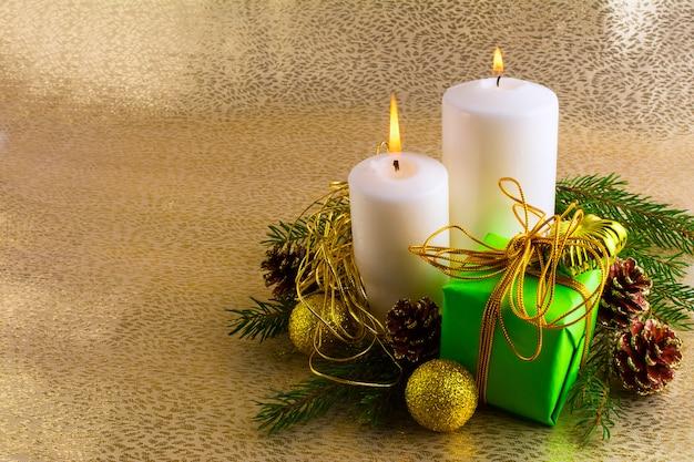 Weihnachtshintergrund mit brennenden kerzen und geschenkbox